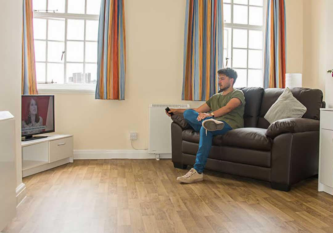 Young person sitting in the lounge watching television